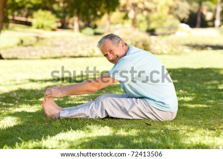 Mature man doing his streches in the park - stock photo