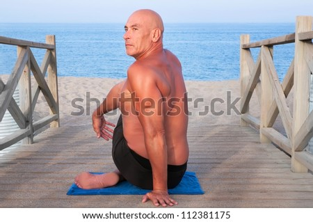 Mature man doing yoga at the beach sitting on a wooden bridge