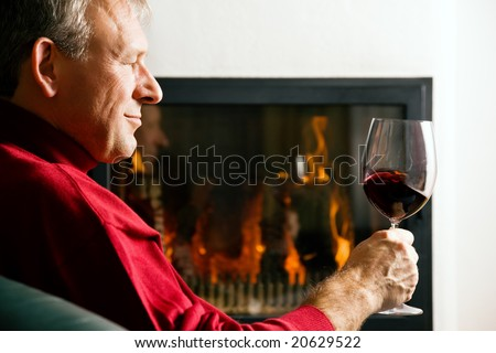 Mature man drinking a glass of read wine in front of his fireplace - stock photo