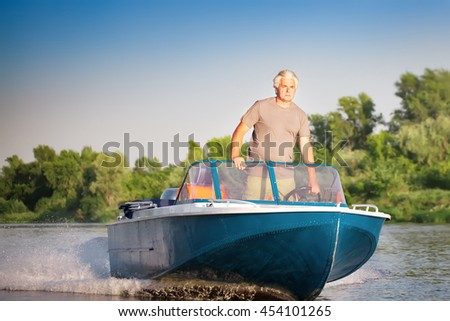 Mature man driving motor boat. - stock photo