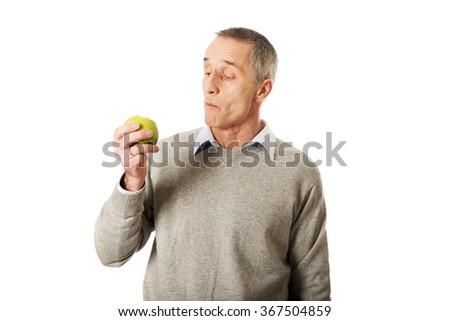 Mature man eating an apple - stock photo