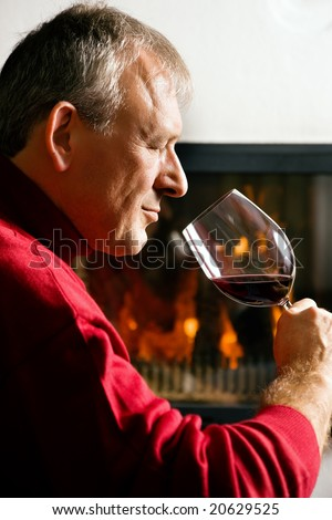 Mature man enjoying a glass of red wine in front of a fire - stock photo