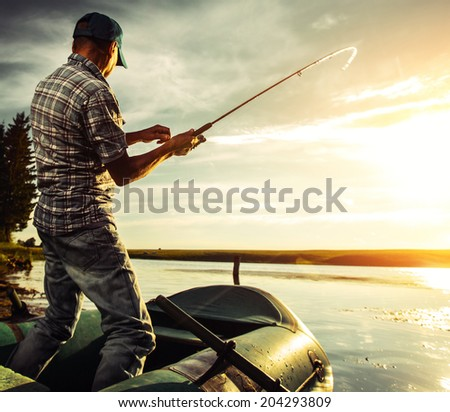 Mature man fishing from the boat at sunset - stock photo