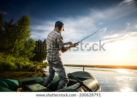 Mature man fishing from the boat on the pond at sunset - stock photo
