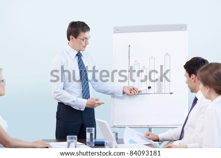 Mature man gives a presentation at the office - stock photo