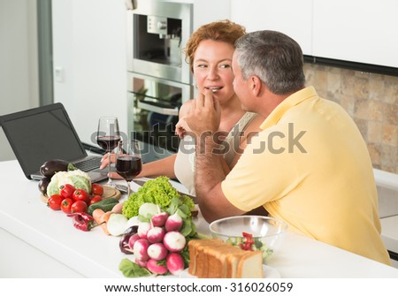 Mature man giving her wife cucumber for tasting. People preparing dishes for lunch or dinner, drinking red wine and looking into laptop computer.