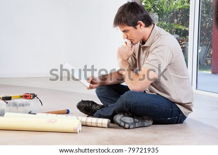 Mature man going through the color swatch while sitting on the floor - stock photo