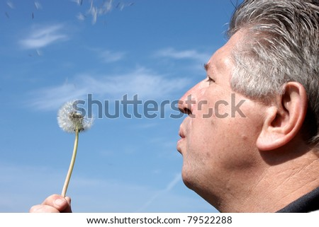 mature man head and shoulders blowing dandelion seeds with blue sky background - stock photo