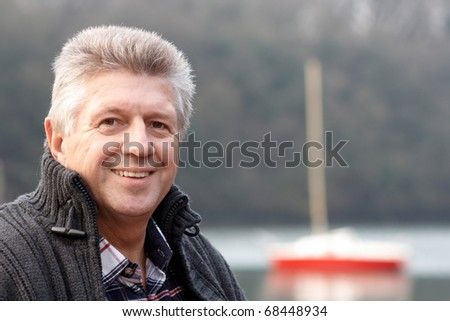 Mature man head and shoulders with boat in the background - stock photo