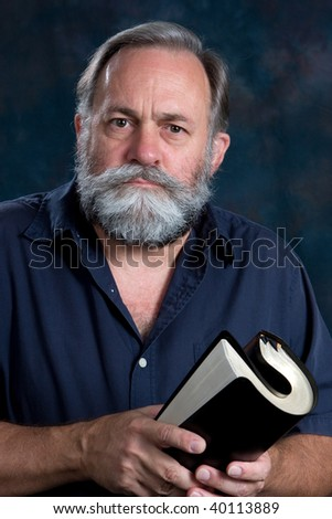 Mature man hold rolled bible in both hands. - stock photo