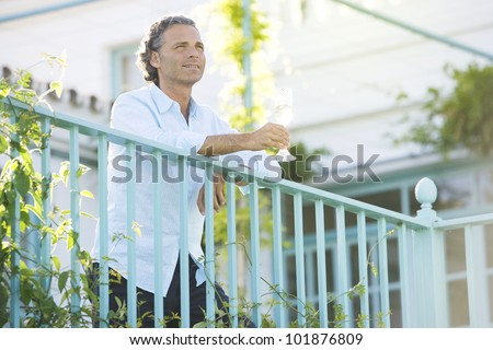 Mature man holding a glass of champagne as he leans on a balcony outdoors.
