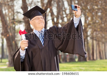 Mature man holding diploma and taking selfie in park - stock photo