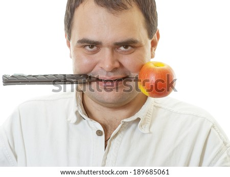 Mature man holds in mouth knife with an apple, is isolated on white background.