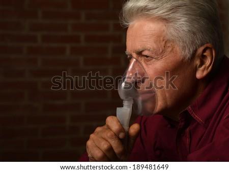 Mature man in a shirt with inhalator - stock photo