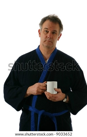 Mature man in bathrobe holding coffee cup - stock photo