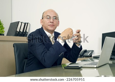 Mature Man in formalwear drinking coffee while sitting at his working place - stock photo