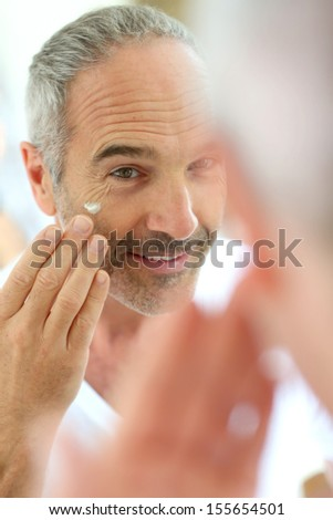 Mature man in front of mirror applying cosmetics - stock photo