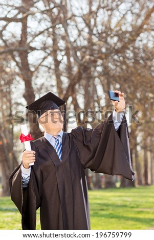 Mature man in graduation gown taking selfie outdoors - stock photo