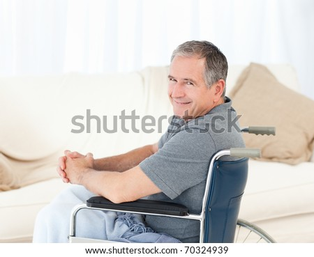Mature man in his wheelchair looking at the camera at home - stock photo