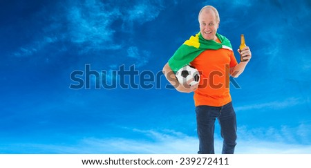 Mature man in orange tshirt holding football and beer against blue sky