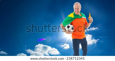 Mature man in orange tshirt holding football and beer against cloudy sky with sunshine