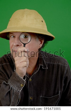 Mature man in pith helmet with a magnifying glass/Mature Explorer/Man is looking through magnifying glass - stock photo