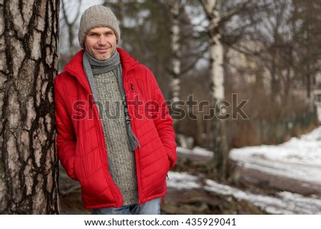 Mature man in winter clothes under a pine tree