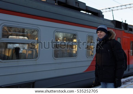 Mature man in winter clothes waiting for commuter train on the railroad station platform