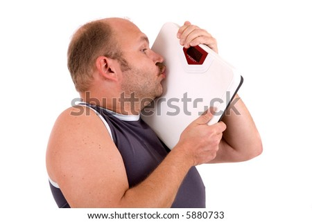 Mature man kissing the weighing scale happy with his weight scale - stock photo