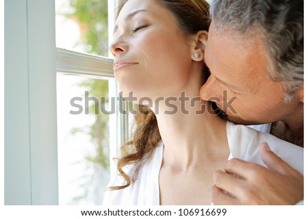 Mature man kissing woman's neck by large french window.