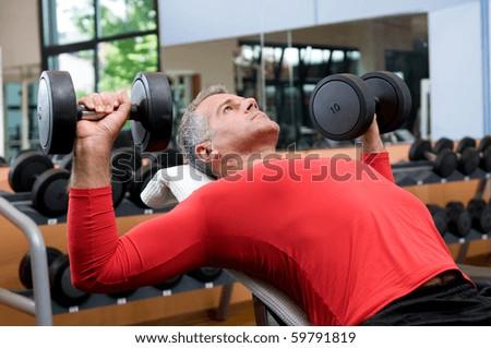 Mature man lifting dumbells at fitness gym - stock photo