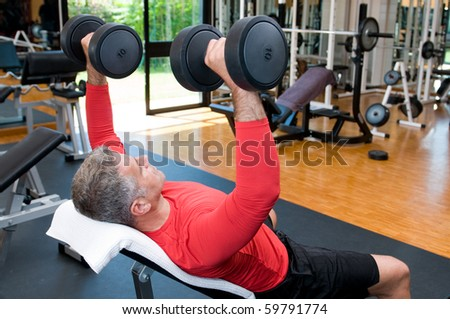 Mature man lifting dumbells at fitness gym, rear view - stock photo