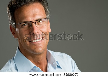 Mature man looking at camera with a bright smile and a pair of glasses. Space for text - stock photo