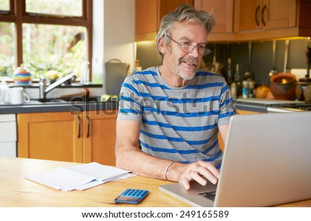Mature Man Looking At Home Finances In Kitchen - stock photo
