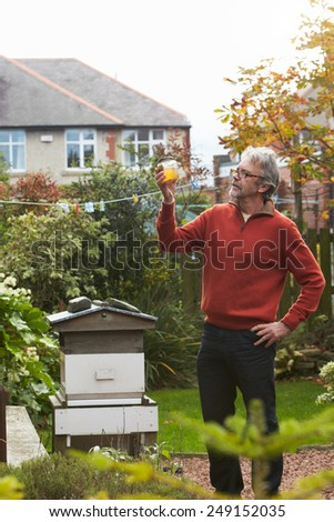 Mature Man Looking At Honey Produced By His Own Bees - stock photo