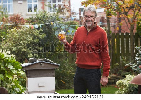 Mature Man Looking At Honey Produced By His Own Bees