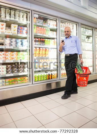 Mature man looking at mobile phone while walking in front of refrigerators in shopping centre - stock photo