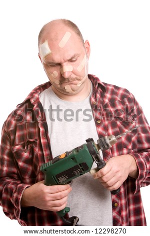 Mature man looking at the drill machine in his hand with a questioning look