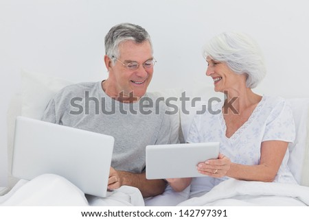 Mature man looking at wifes tablet pc in bed - stock photo