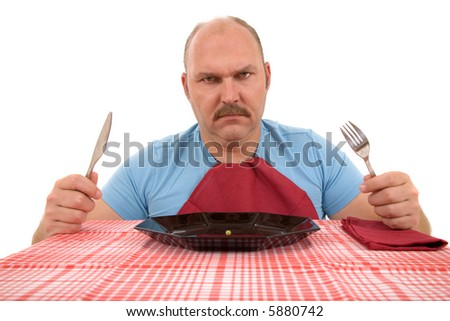 Mature man looking very angry with the content of his plate - stock photo