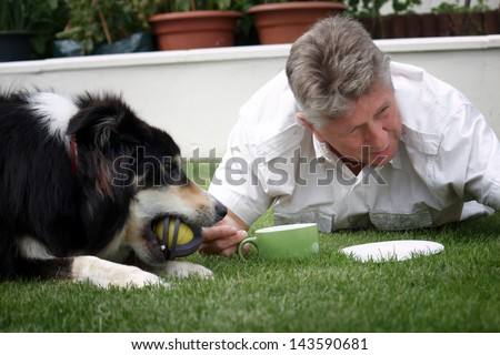 Mature man lying on the grass with border collie