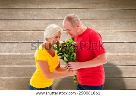 Mature man offering his partner flowers against wooden surface with planks