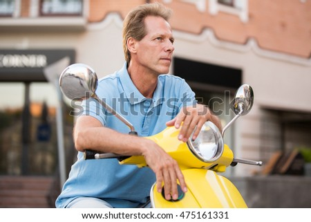 Mature man on a scooter. Guy with serious face expression. Tourist makes a short break. What is my next destination.