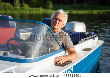 Mature man on driving motor boat.
