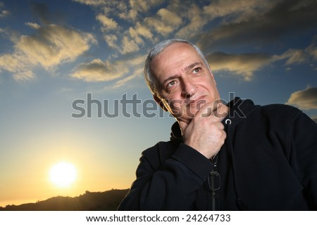 Mature man outdoors, thinking - stock photo
