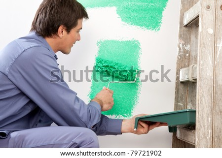 Mature man painting the wall with a roller while holding a paint can - stock photo