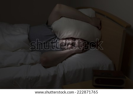Mature man, pillow over head with eyes wide open, cannot sleep at night from insomnia - stock photo