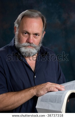 Mature man poses with a serious look with his hand on the bible. - stock photo