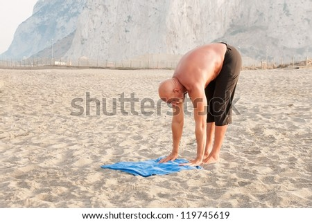 Mature man practicing yoga at the beach stretching arms and legs