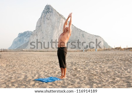 Mature man practising yoga at the beach with the rock of gibraltar as background exercising for balance of body and mind